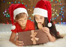 Petits enfants mignons dans des chapeaux de Santa ouvrant le boîte-cadeau de Noël Images libres de droits