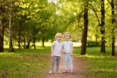 Petits enfants mignons jouant ensemble et tenant des mains dans ensoleillé photos stock