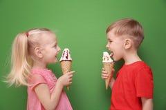 Petits enfants mignons mangeant la crème glacée sur le fond de couleur Images stock