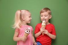 Petits enfants mignons mangeant la crème glacée sur le fond de couleur Photo stock