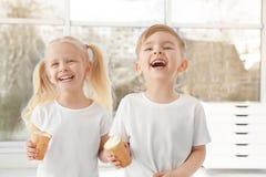 Petits enfants mignons mangeant la crème glacée sur le fond de fenêtre Image stock