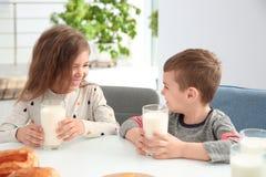 Petits enfants mignons prenant le petit déjeuner avec du lait Photo libre de droits