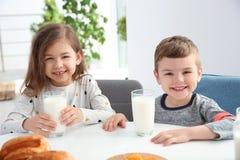 Petits enfants mignons prenant le petit déjeuner avec du lait Photographie stock