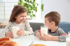 Petits enfants mignons prenant le petit déjeuner avec du lait Photo stock
