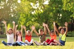 Petits enfants mignons s'asseyant sur l'herbe dehors Photo libre de droits