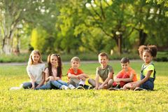 Petits enfants mignons s'asseyant sur l'herbe dehors Photos libres de droits