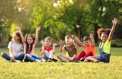 Petits enfants mignons s'asseyant sur l'herbe dehors Photos stock