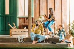 Petits enfants mignons s'asseyant sur le porche avec différents articles de déplacement Photos stock