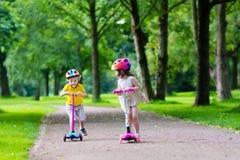 Petits enfants montant les scooters colorés Photo libre de droits