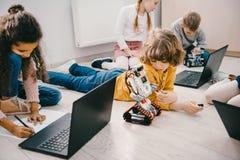 petits enfants programmant avec des ordinateurs portables tout en se reposant sur le plancher, tige photographie stock libre de droits