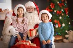 Petits enfants recevant des cadeaux de Santa Claus authentique image stock