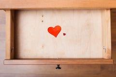 Petits et grands coeurs rouges dans le tiroir ouvert Images stock