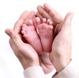 Petits feets de chéri se trouvant sur des mains du `un s de père Image libre de droits