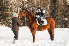 Petits fille, entraîneur de cheval et cheval en hiver Image libre de droits