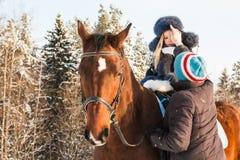 Petits fille, entraîneur de cheval et cheval en hiver Image stock
