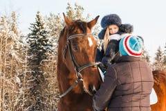 Petits fille, entraîneur de cheval et cheval en hiver Images stock