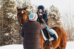 Petits fille, entraîneur de cheval et cheval en hiver Photo libre de droits