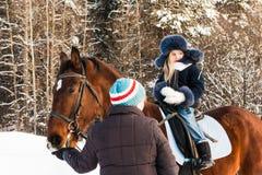 Petits fille, entraîneur de cheval et cheval en hiver Images libres de droits