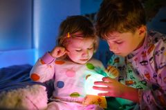 Petits fille mignonne d'enfant en bas âge et garçon d'enfant jouant avec la lampe colorée de lumière de nuit avant d'aller au lit image stock