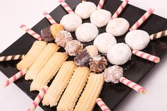 Petits fours, cakes and biscuits. Cakes, biscuits and petits fours presented in a black dish Royalty Free Stock Photography