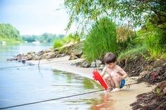 petits frères jouant avec les bateaux de papier par une rivière le jour chaud et ensoleillé d'été Photos libres de droits