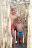 Petits frères jouant sur la plage dans une hutte en bambou Images libres de droits
