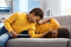 Petits frères joyeux chatouillant un un autre sur le sofa Images libres de droits