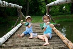 Petits frères jumeaux adorables s'asseyant sur un pont en bois et jugeant un filet plein des poissons au lac Images stock