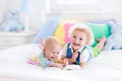 Petits frères lisant un livre dans le lit Images stock