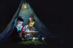 Petits frères mignons, jouant au comprimé et au téléphone la nuit i Photo stock