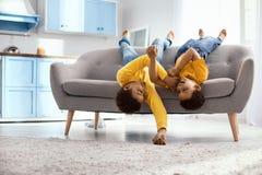 Petits frères optimistes se trouvant sur le divan et se chatouillant Photos libres de droits
