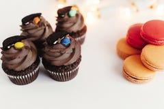 Petits gâteaux élégants de chocolat avec le biscuit et la sucrerie sur le dessus et le colo Image stock