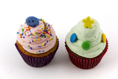 Petits gâteaux avec de la crème rose et verte d'isolement sur le fond blanc Images stock