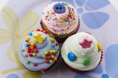 Petits gâteaux avec de la crème rose et verte sur le fond blanc Image libre de droits