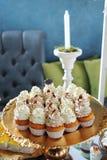 Petits gâteaux avec le fondant blanc sur le plateau argenté Photographie stock libre de droits