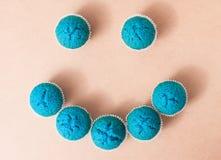 Petits gâteaux bleus disposés sous forme de smiley Image libre de droits