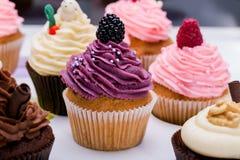 Petits gâteaux colorés avec différents goûts Petits beaux gâteaux sur le dessus de table blanc Fin vers le haut Image libre de droits