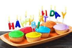 Petits gâteaux colorés de joyeux anniversaire avec des bougies Photos stock