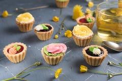 Petits gâteaux colorés de plat et de table gris Images stock