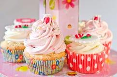 Petits gâteaux colorés sur un support rose Images stock