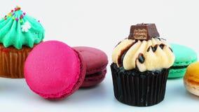 Petits gâteaux délicieux et macarons colorés se déplaçant sur le fond blanc banque de vidéos