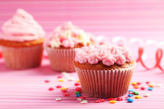 Petits gâteaux d'anniversaire avec de la crème de beurre sur le fond coloré Images stock