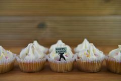 Petits gâteaux d'Eastertime avec une figurine miniature de personne tenant un signe pour Joyeuses Pâques Photo libre de droits