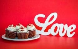 4 petits gâteaux de chocolat avec AMOUR blanc se connectent un fond rouge Photographie stock libre de droits
