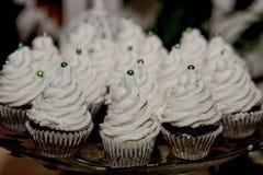 Petits gâteaux de chocolat avec de la crème blanche sur le plateau images stock