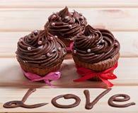 Petits gâteaux de chocolat avec de la crème de chocolat, décorée du ruban, sur un fond en bois avec l'amour d'inscription Image stock