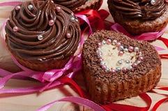 Petits gâteaux de chocolat avec de la crème de chocolat et le petit gâteau sous forme de coeur, décoré du ruban, sur un fond en b Photographie stock libre de droits