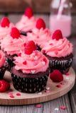 Petits gâteaux de chocolat avec de la crème rose, des coeurs de sucre et des framboises fraîches pour Valentine Day photographie stock
