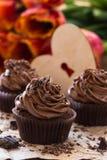 Petits gâteaux de chocolat de jour de mères avec des tulipes de ressort et h en bois photos stock