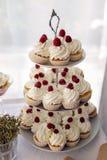Petits gâteaux de finition avec de la crème et les framboises blanches Photographie stock
